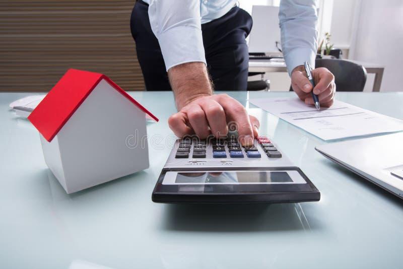 Человеческая рука расчетливое Билл с калькулятором стоковые фотографии rf