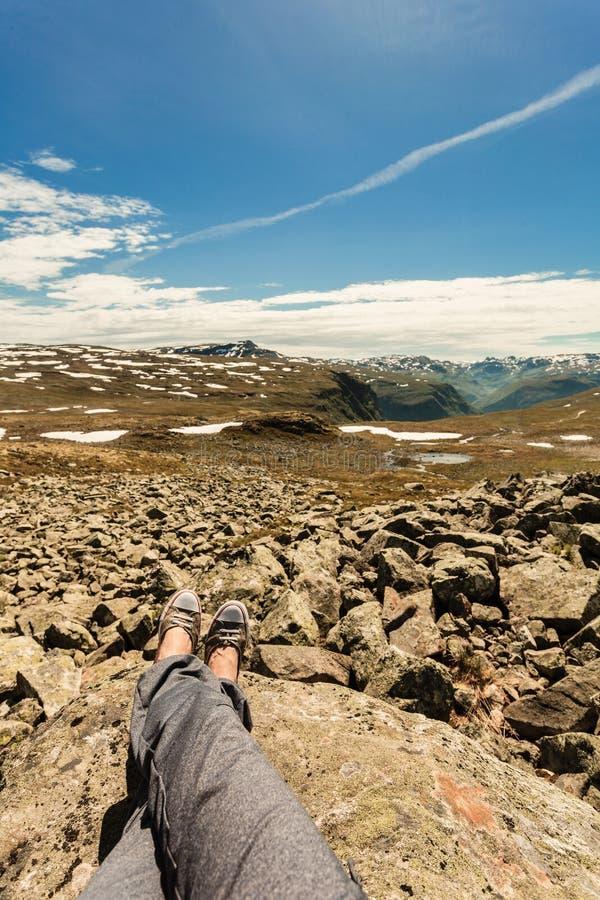 Человеческие ноги и ландшафт гор в Норвегии стоковое изображение rf