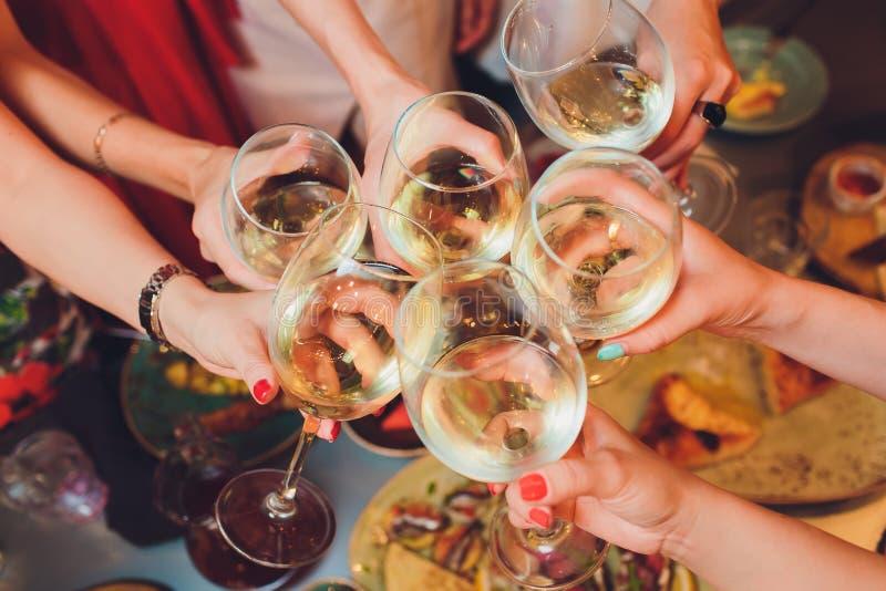 Человеческие руки со стеклами красного вина clinking они над, который служат таблицей стоковая фотография rf