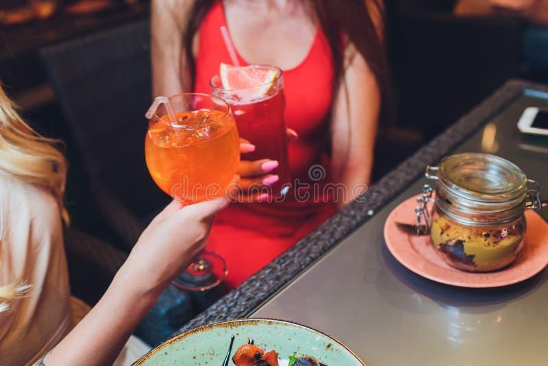 Человеческие руки со стеклами красного вина clinking они над, который служат таблицей стоковая фотография