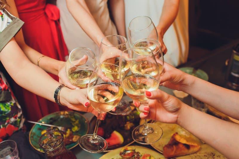 Человеческие руки со стеклами красного вина clinking они над, который служат таблицей стоковые фото