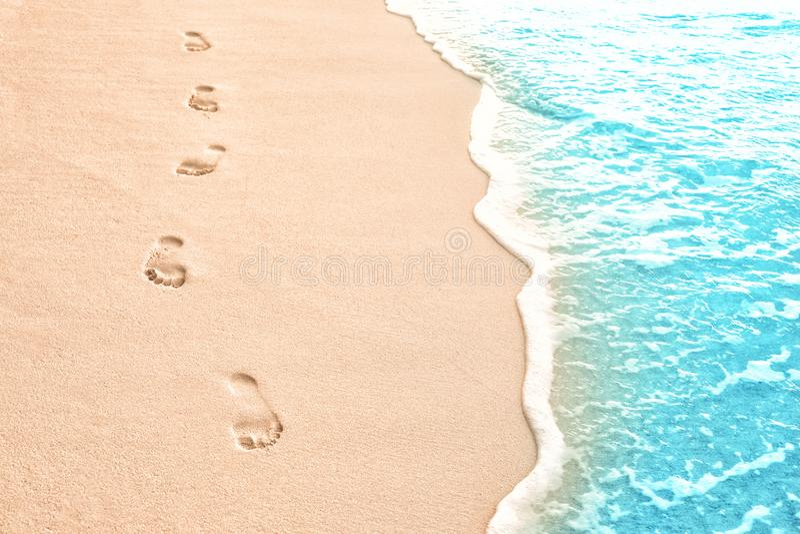Человеческие следы ноги на песке пляжа на курорте стоковые фотографии rf