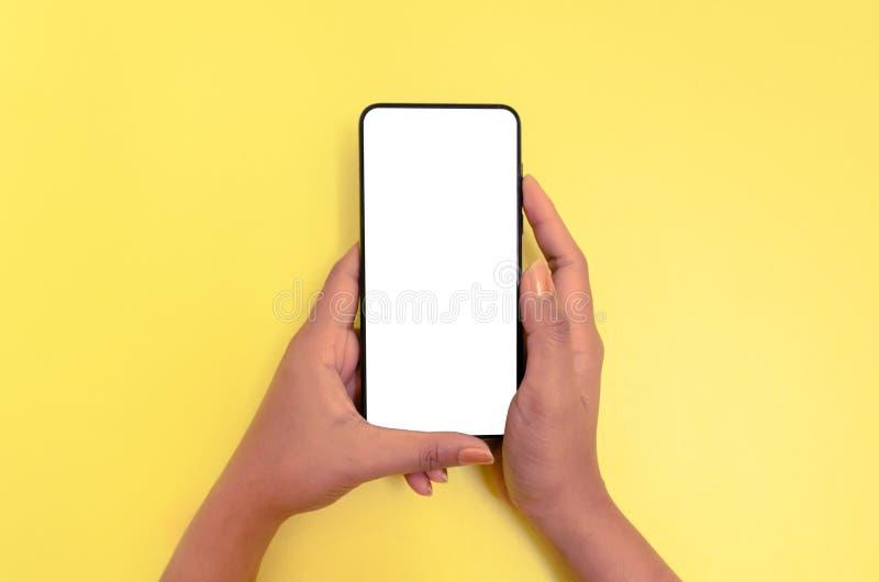Человеческий смартфон удерживания руки с белой предпосылкой экрана стоковое изображение rf