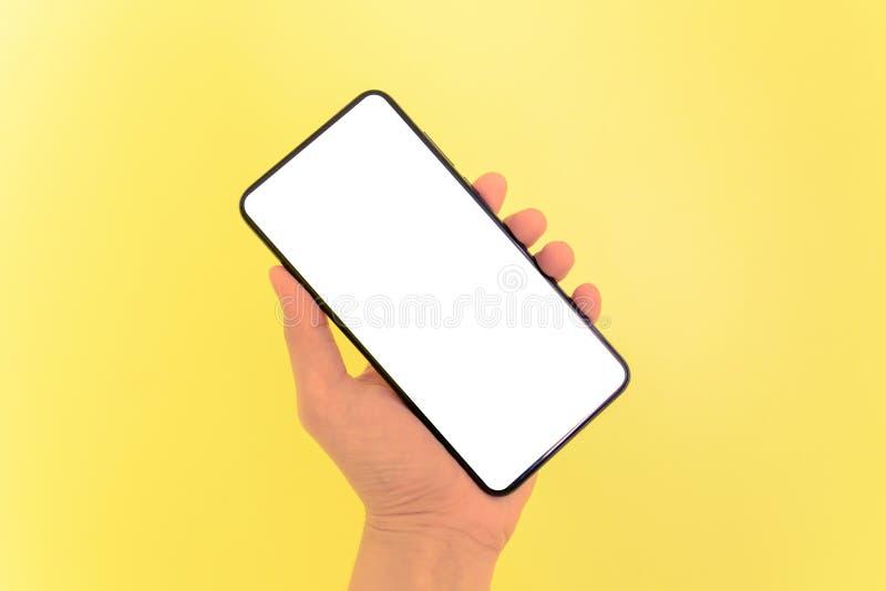 Человеческий смартфон удерживания руки с белой предпосылкой экрана стоковое фото rf