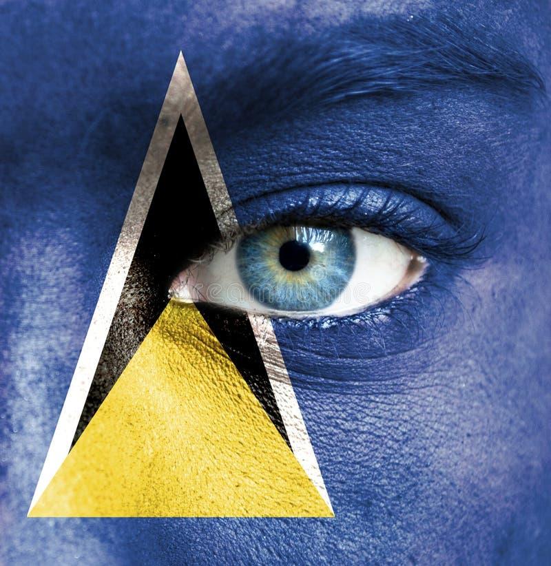 Человеческое лицо покрашенное с флагом Сент-Люсия стоковые фото