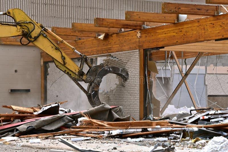 Челюсти копая экскаватором машины разрушить кирпичную стену стоковая фотография
