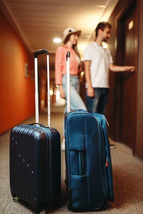 Чемоданы в прихожей гостиницы, паре раскрывают дверь стоковые фото