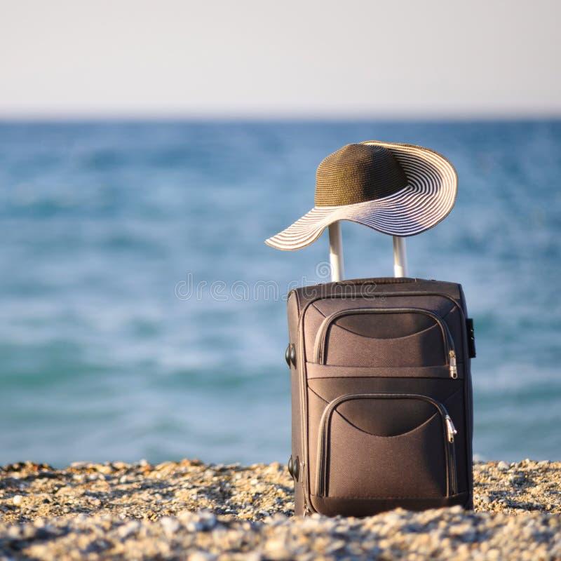 Чемодан и шляпа на пляже стоковая фотография