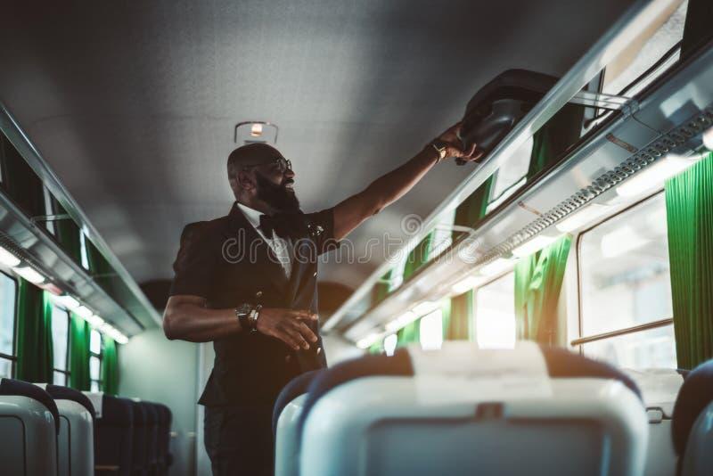 Чемодан рудоразборки черного парня в поезде стоковые фото