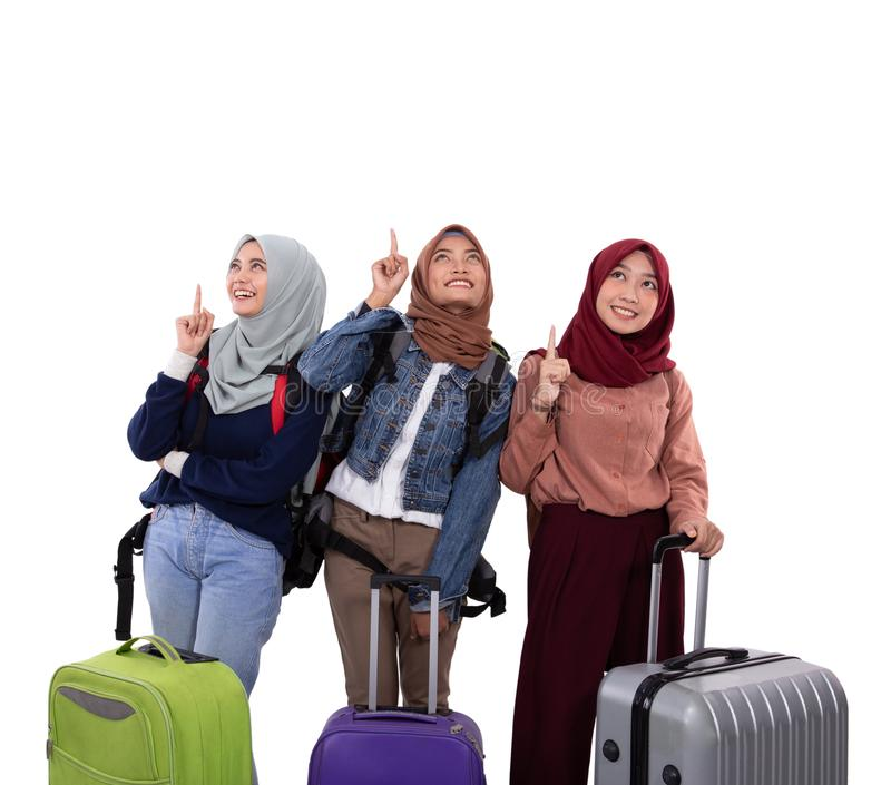 Чемодан удерживания положения женщины 3 hijab и сумка нося с указывать рук стоковое фото rf