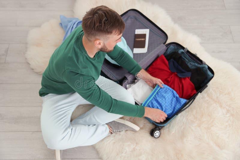 Чемодан упаковки молодого человека для путешествия лета стоковые фото