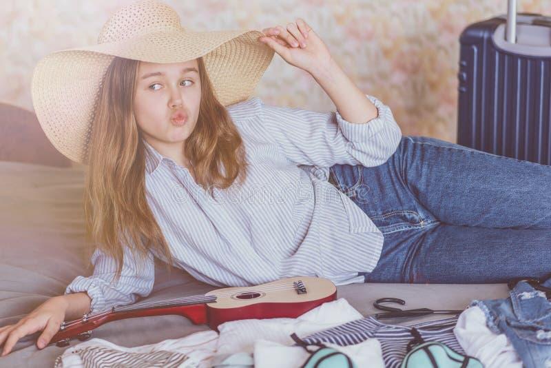Чемодан упаковки молодой женщины дома стоковые изображения