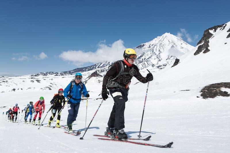 Чемпионаты альпинизма лыжи: подъем альпиниста лыжи группы на лыжах на вулкане предпосылки стоковое изображение