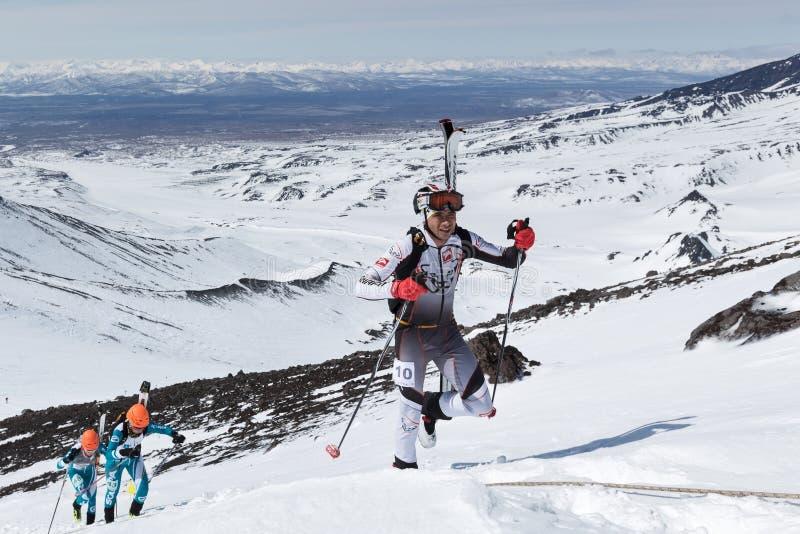 Чемпионаты альпинизма лыжи: подъем альпиниста лыжи к горе при лыжи связанные к рюкзаку стоковые фотографии rf