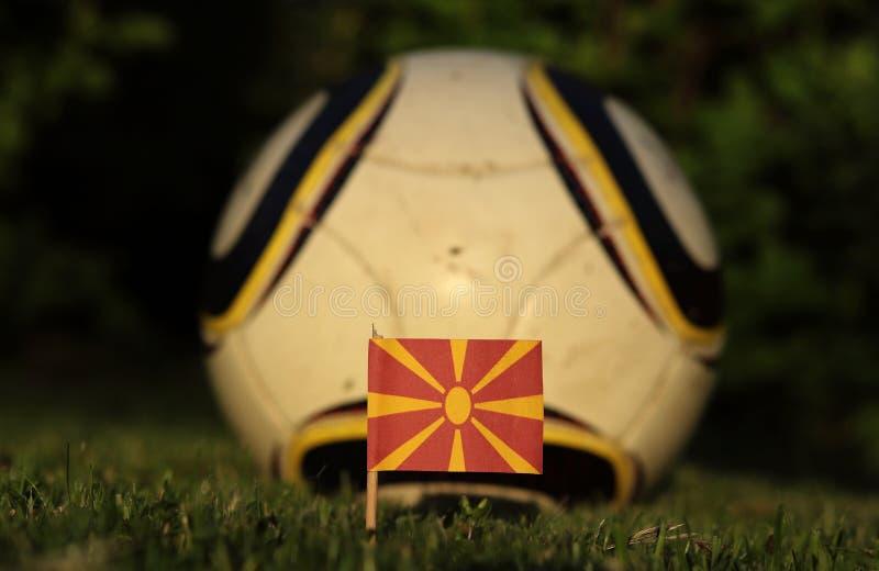 Чемпионат мира по футболу 2022 Евро-2020 Македонский флаг на футбольной площадке с белым шаром Флаг македонского солнца стоковое фото rf