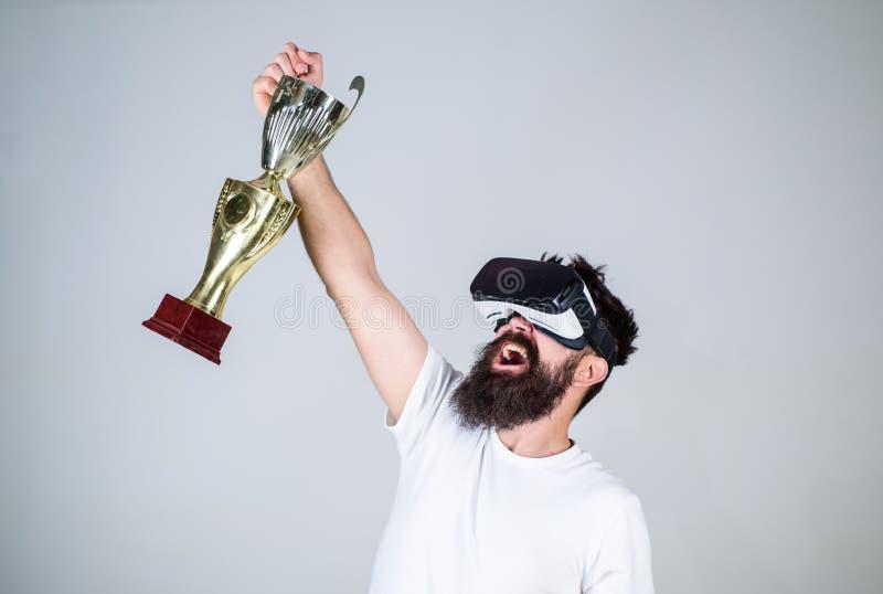Чемпионат онлайн Шлемофон vr битника человека бородатый держит золотой кубок Победа чувства в играх виртуальной реальности достиг стоковое изображение rf