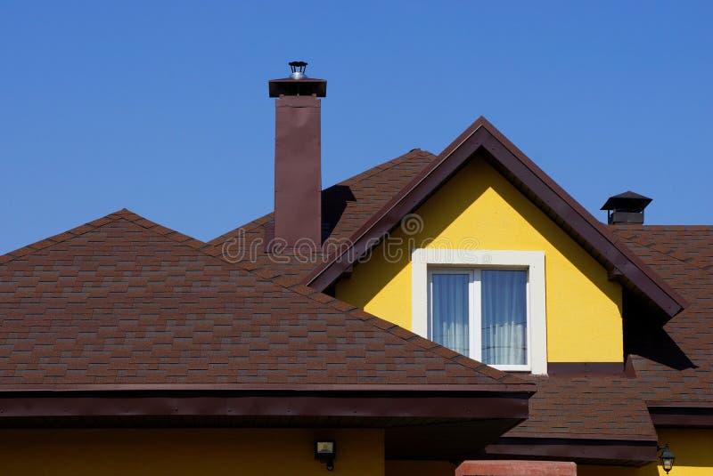 Чердак желтого дома с окном и коричневой крыть черепицей черепицей кр стоковые фото