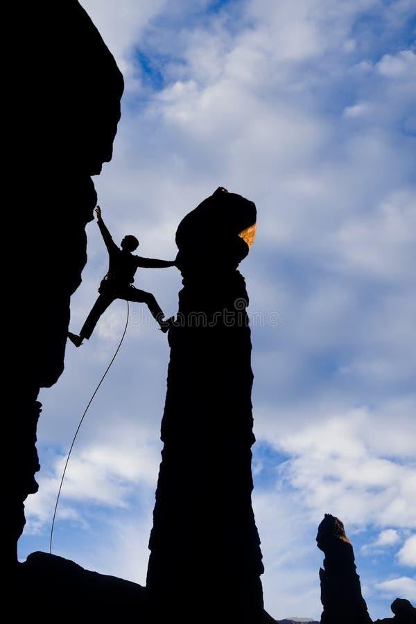 через зазор альпиниста достигая утес стоковые изображения