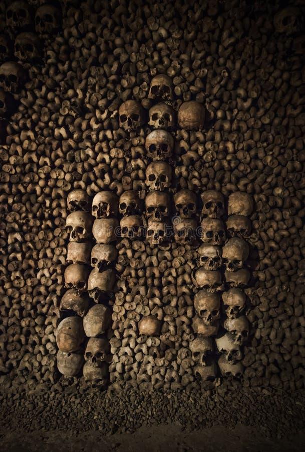 Черепа и косточки в катакомбах Парижа, Франции стоковое фото