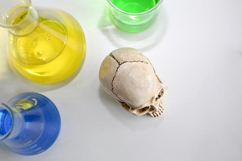 Череп и шприц медицинские пробирки, череп и расплывчатый шприц Медицинский риск злоупотребления и смерти вируса стоковые изображения