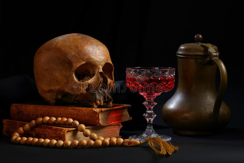 Череп, книги, стекло красного вина и бронзовый кувшин стоковые изображения