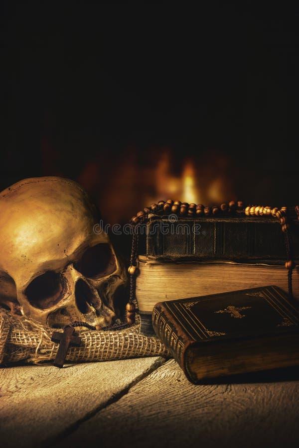 Череп с розарием и библией перед камином стоковые изображения rf