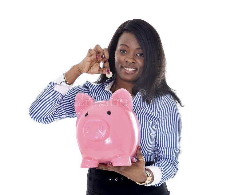 Черная Афро-американская бизнес-леди кладя монетку в огромное розовое piggybank стоковые изображения rf