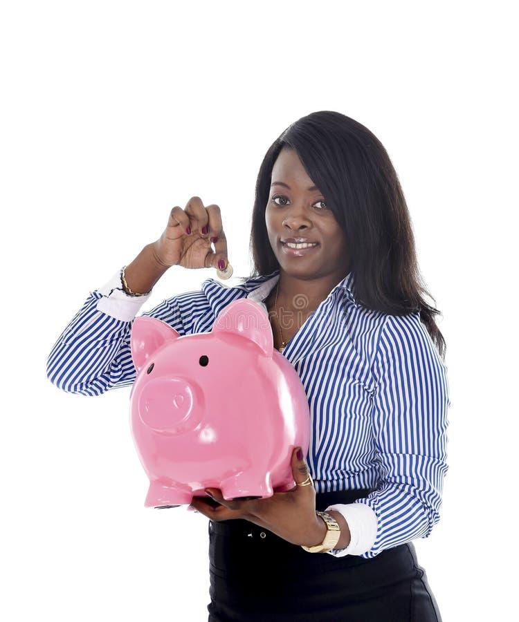 Черная Афро-американская бизнес-леди кладя монетку в слишком большое розовое piggybank стоковое изображение