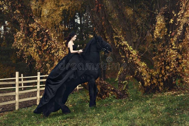 Черная ведьма ферзя верхом на черной лошади в хмуром лесе стоковое фото