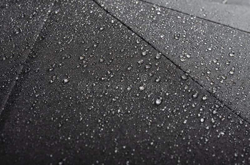 Черная водоустойчивая текстура зонтика с капельками воды стоковое изображение rf