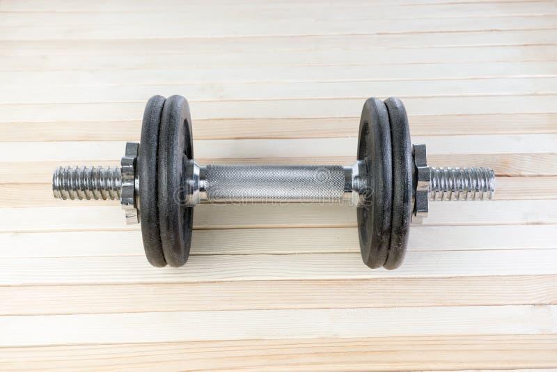 Черная гантель спортзала металла с ручкой хрома серебряной на деревянной предпосылке с высоким разрешением Принципиальная схема п стоковые изображения rf