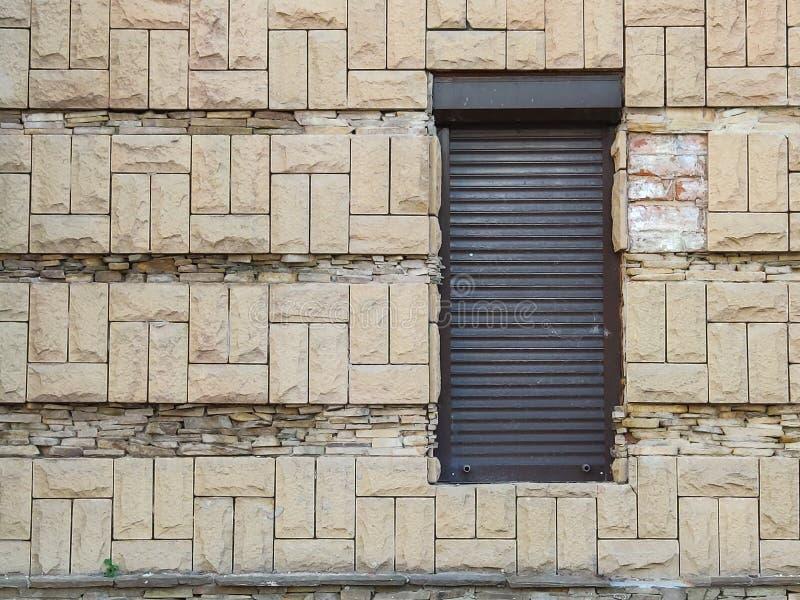Черная дверь крен-металла против старой светлой кирпичной стены, проход к магазину или театр, задний выход стоковое изображение rf