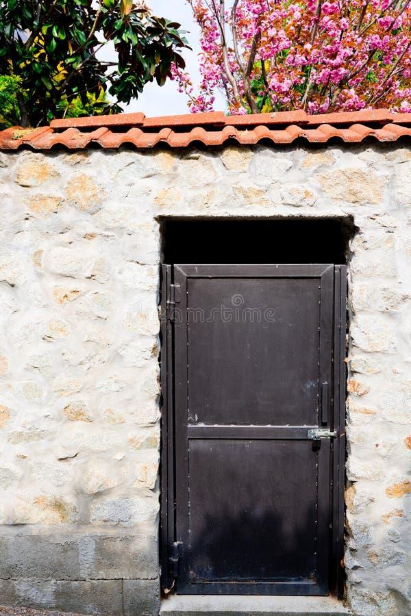 Черная дверь металла внутри стена утеса стоковое изображение rf