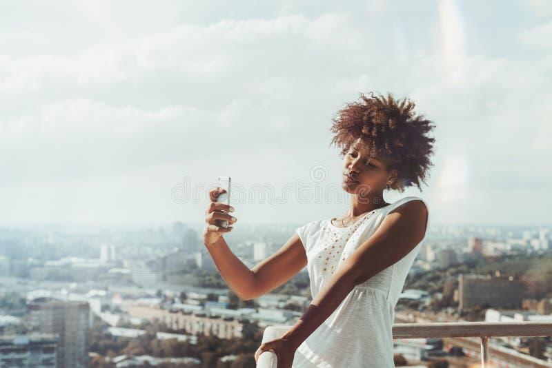 Черная девушка принимая selfie на балконе высотного здания стоковые изображения