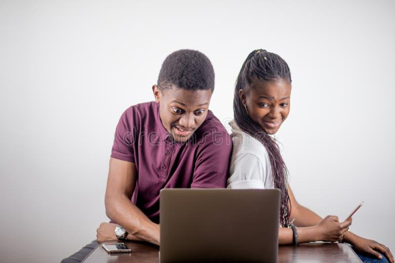 Черная девушка сидя перед компьтер-книжкой s смотря на экране стоковое изображение rf
