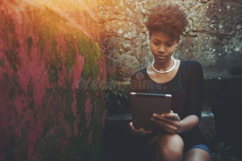 Черная девушка старшекурсника на шаге лестницы с цифровой пусковой площадкой стоковые фотографии rf
