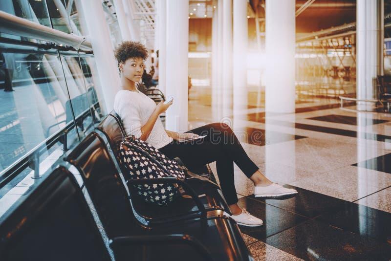 Черная девушка с smartphone в торговом центре стоковое фото