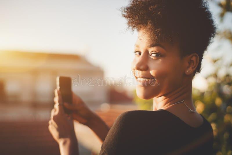 Черная девушка фотографирует на ее smartphone стоковая фотография
