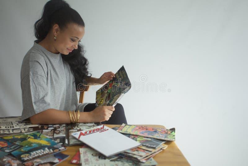 Черная девушка читая собрание комиксов стоковое изображение