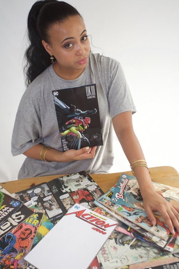 Черная девушка читая собрание комиксов стоковое изображение rf