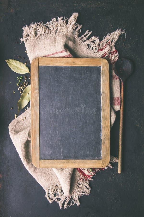 Черная доска, деревянная ложка и специи - варить предпосылку стоковое изображение rf