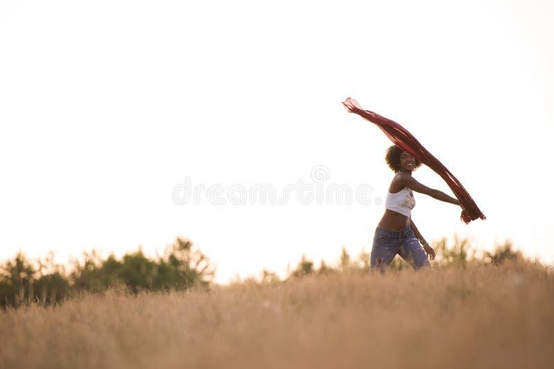 Черная девушка танцует outdoors в луге стоковая фотография