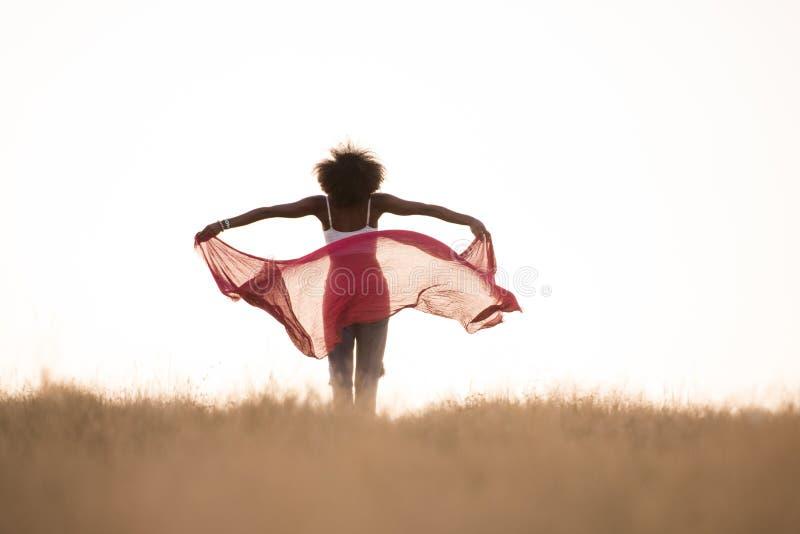 Черная девушка танцует outdoors в луге стоковое изображение rf