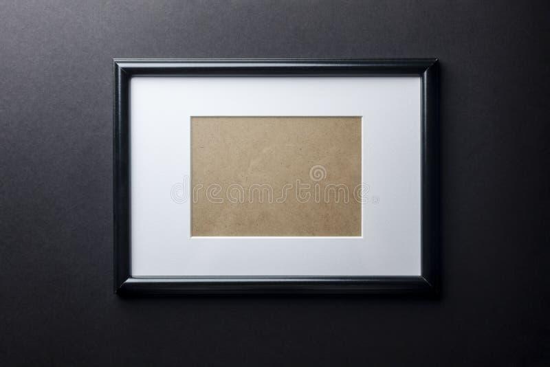 Черная деревянная рамка на черной стене стоковые изображения
