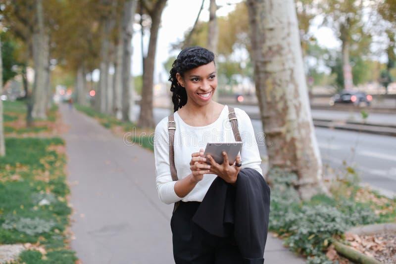 Черная женщина gladden студент идя и используя таблетку около улицы с деревьями стоковые изображения rf