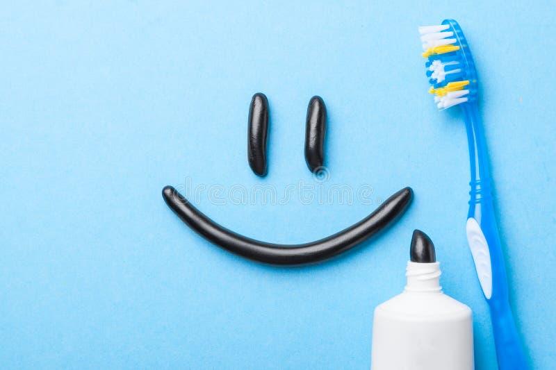 Черная зубная паста от угля для белых зубов Зубная паста в форме улыбки на стороне, трубке и зубной щетке на сини стоковое фото rf