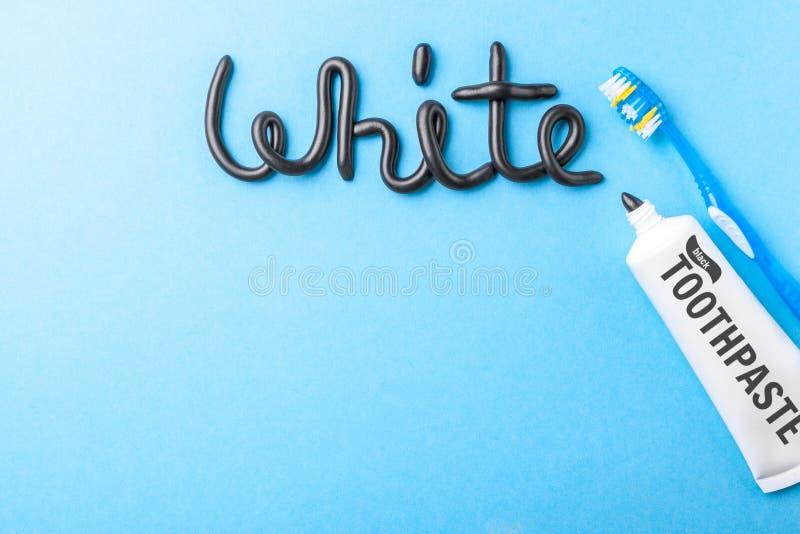 Черная зубная паста от угля для белых зубов Сформулируйте БЕЛИЗНУ от черных зубной пасты, трубки и зубной щетки на сини стоковые фотографии rf