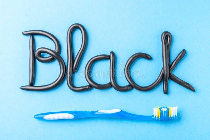 Черная зубная паста от угля для белых зубов Сформулируйте ЧЕРНОТУ от зубной пасты и зубной щетки на сини стоковое фото