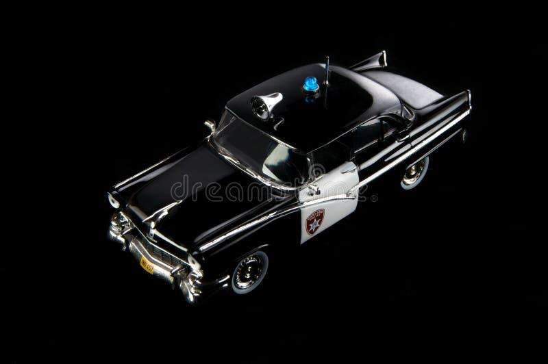 Черная игрушка, пластиковая модель полицейской машины Черная предпосылка стоковое изображение rf