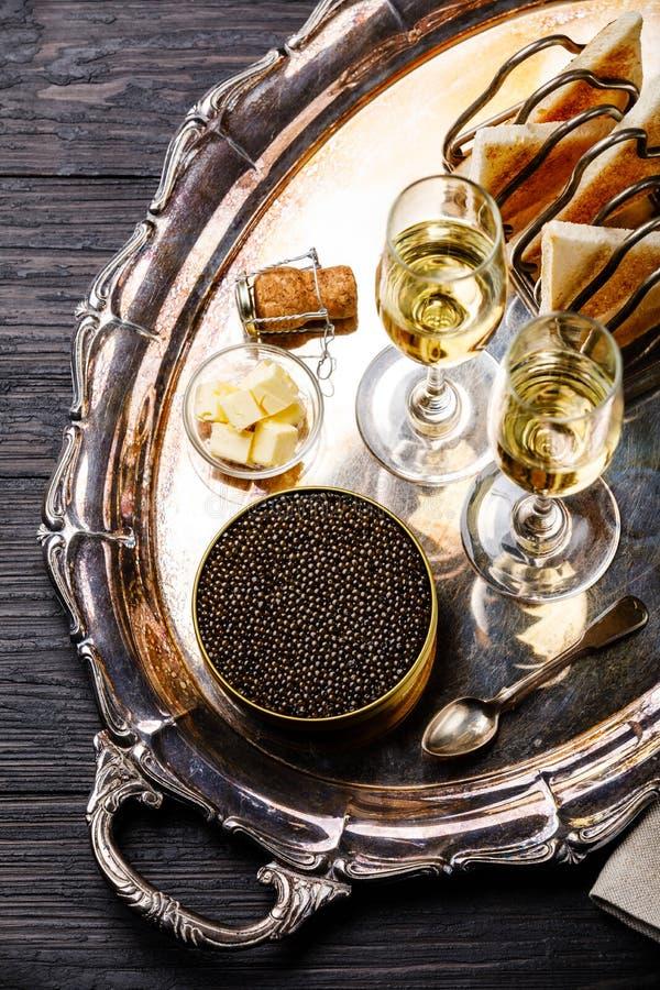 Черная икры чонсервная банка внутри, здравица свежего хлеба и шампанское стоковые фотографии rf